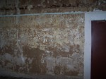 Exposed plaster on eastern wall