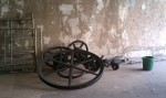 Wheel and gearing, next to a regular sized bucket